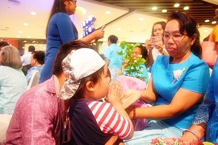 A young boy 'wais' his grandmother after his parents had already presented jasmine flowers, one of the activities in the Love to 80 Outstanding Mothers in Pattaya celebration at Central Festival Pattaya Beach.