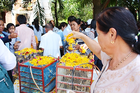 People earn merit by showering flowers over bird cages to spare their lives.