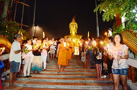 Revered monks begin the Wien Thien ceremony, carrying lighted candles three times around Wat Phra Yai.