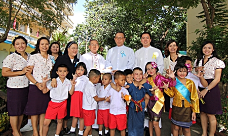 Children and care givers pose for a commemorative photo with Bishop Emeritus Thienchai Samanjit (center), along with Father Veera Phangrak and Father Kritsada Sukkaphat.