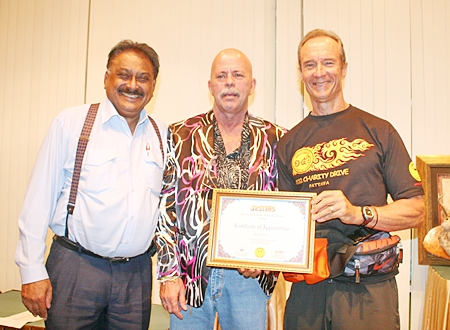 """Tournament organizer Mark Gorda, center, receives a certificate of appreciation from Jesters Care For Kids representative Lewis """"Woody"""" Underwood, right, while Peter Malhotra, MD of media sponsors Pattaya Mail Media stands left."""