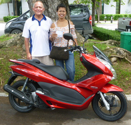 Jester Bill Freeman presents the Honda PCX 150, top prize in this year's grand raffle, to winner Bam from the Saloon Bar.