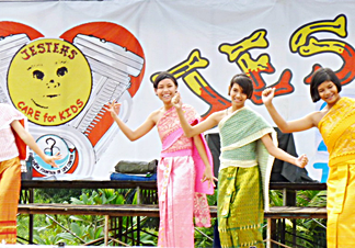 Girls from Ban Jing Jai Orphanage perform a traditional Thai dance after the rain stopped and the sun came out at the fair last year.