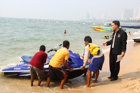 Mayor Itthiphol Kunplome inspects a jet ski and talks with the vendors on Pattaya Beach.