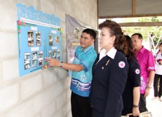 Red Cross President Bussarawadee Ekachai is shown plans to refurbish or build houses for poor people in Banbung and Panthong districts.