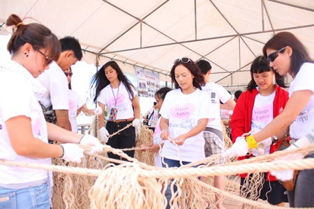 Kamonwan Wipulakorn (center) helps make the artificial trees from ropes.