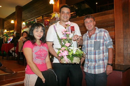 (L to R) Allan Ottesen (centre) who now runs the business for his mom and dad receives a bouquet  from well-wishers.