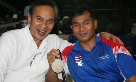 Supachai Kousub shows his silver medal to principal of the Vocational School, Udomchoke Churut.