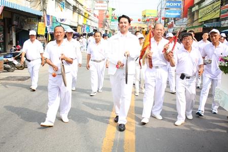 Prasit Thongthitcharoen (left), vice president of the Sawang Boriboon Thammasathan Foundation, and Mayor Itthiphol Kunplome sound their gongs whilst leading the lions and dragon parade through New Naklua market.