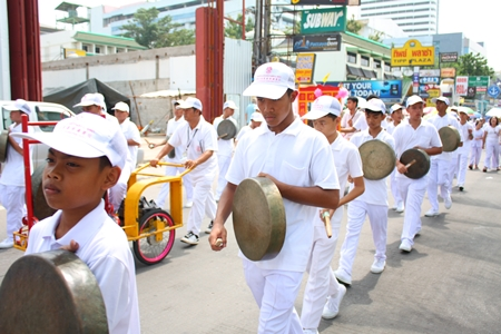 White clad marchers sound the gong to alert people in the area that the parade is marching through.