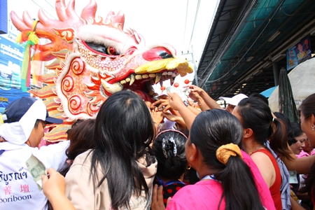 People scramble to feed the dragon and make merit.