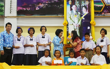 Tharinee Jiaranaipong (3rd right), director of Wat Chaiyamongkol Preschool, greets Aaporn Rajsingho (4th right), director of Pattaya School No. 8, and students who received scholarships.