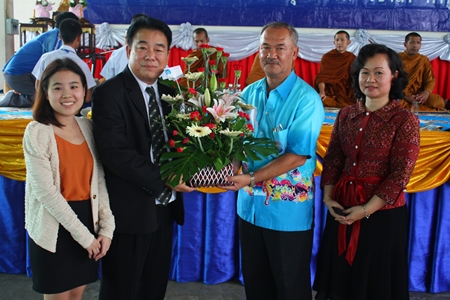 Suwat Rotchatwattanakul (2nd left), vice president of Nongprue PAO, presents flowers congratulating Suwat Nongyai, school licensee, with Waraporn Jandech, director of Pattaya Arunothai School, on the school's 40th Anniversary.