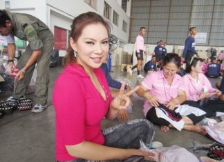 Former Miss Thailand World Panadda Wongphudee helps pack relief supplies for flood victims.