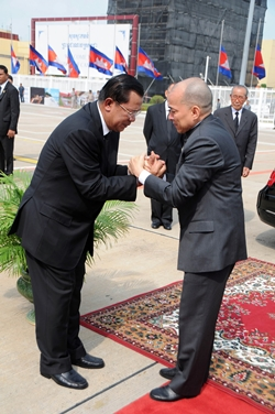 In this photo released by China's Xinhua News Agency, Cambodian King Norodom Sihamoni, right, shakes hands with Cambodian Prime Minister Hun Sen at the airport in Phnom Penh on Monday, Oct. 15, 2012. Sihamoni and Hun Sen flew to Beijing on Monday morning to retrieve the body of former King Norodom Sihanouk who died at the age of 89. (AP Photo/Xinhua, Zhao Yishen)