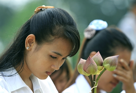 Cambodian students hold lotus flowers while praying in front of the main gate of the Royal Palace in Phnom Penh, Cambodia, to mourn the death of former King Norodom Sihanouk Tuesday, Oct. 16, 2012. (AP Photo/Heng Sinith)