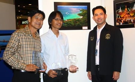 "Mayor Itthiphol Kunplome and Sawat Pattiphanprasert, president of the Federation of Photographic Associations of Thailand, congratulate Sanchai Lungrung, who's photo ""Sawan Tawanork"" (background) won Pattaya's second-annual photo contest."