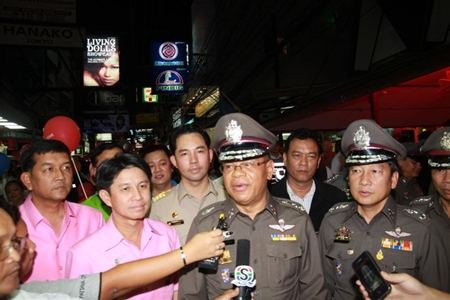 Reporters converge on police officials doing a walk through of Walking Street.
