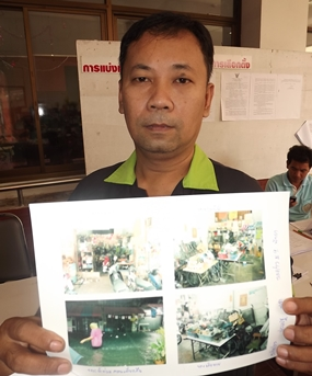 Flood victim Prasert Sornkhum, 43, shows photos of the flood damage at his home, evidence to support receiving relief from City Hall.