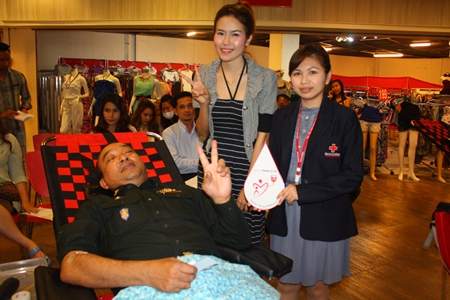 Pol. Lt. Gen. Passorn Ingsrangkul Na Ayuthaya (seated), special advisor to the Royal Thai Armed Forces, is cheered on by Phanisra Sukhjinda (right), acting chief of National Blood Center 3, and Kusuma Aebata (center), promotion officer of Central Festival Pattaya Beach as he gives blood.