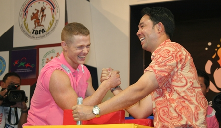 Pattaya mayor Ittipol Kunplome, right, tests his arm-wrestling prowess against one of the match referees.