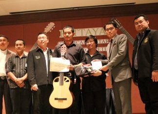 Natdanai Phuaphanprasong (center) receives his prize guitar after winning the 2012 Pattaya Guitar Festival.