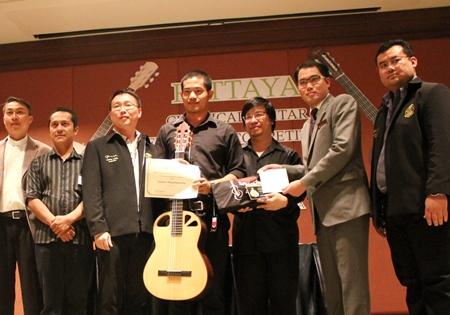 Natdanai Phuaphanprasong (center) receives his prize guitar after winning the 2012 Pattaya Guitar Festival.