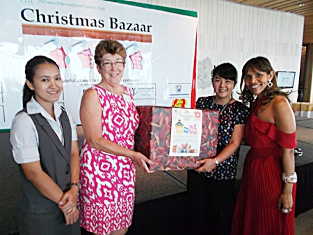 Central Festival presents toy collection totals to PILC president, Ann Winfield, and Ananya Welland, the special events chairperson