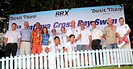 Neoh Kean Boon (3rd right), resident manager of Dusit Thani Pattaya poses for a photo with officials and some of the winners of the 9th Pattaya Cross Bay Swim. Dusit Thani Pattaya has sponsored beach towels and other essentials, buffet lunch for the swimmers and event organizers since the charity swim held its debut nine years ago.