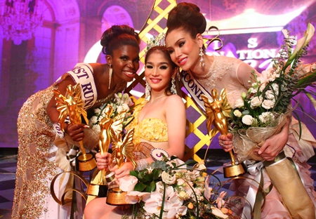 First runner-up Jessika Simoes of Brazil (left) and second runner-up Panvilas Mongkol of Thailand (right) congratulate Miss International Queen 2012 Kevin Balot from the Philippines.