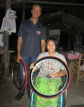Jaruwan quickly settled into her 'new' wheelchair. Woody and Jaruwan are holding the set of spare tires for her wheelchair.
