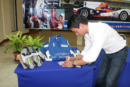 Tor Graves signs the jumpsuit, gloves and shoes he used in this year's FIA World Endurance Championships.