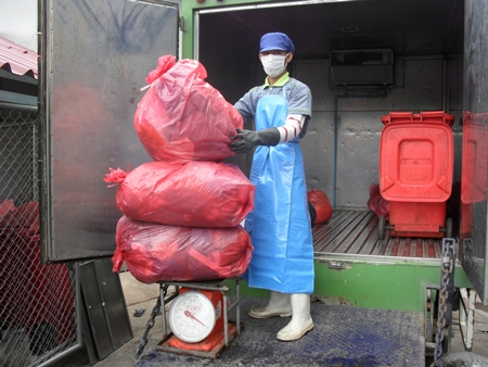 Nattapol Theerawuthiworawet carefully weighs medical waste in preparation to properly dispose of it.