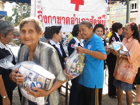 Happy residents pick up aid bags distributed through the Sattahip 'Smile Mobile' service program.