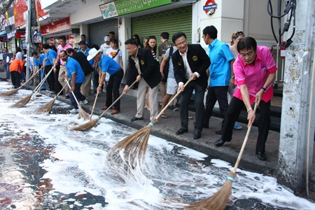 "City officials grab brooms for a photo op to kick off this month's Walking Street ""Big Cleaning Day""."