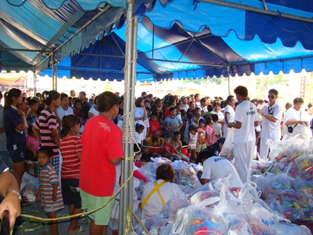 Sawang Boriboon Thammasathan workers distribute to the poor 1,700 packages of food and necessities donated by attendees of its annual vegetarian festival.