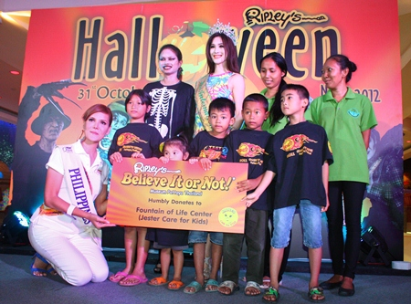 Screaming contest winner Stefania Cruz (left), along with Ripley's World Pattaya Marketing Manager Pathommarat Yimprasert (standing left), and Miss International Queen 2011 Sripassorn Attayakorn (standing center), present cash won from Ripley's Screaming Contest to children from the Fountain of Life Center.