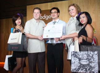 Hotel operations director Gerard Walker (2nd left) and Peta Ruiter (2nd right), director of business development, present Dr. Kitikhun Roongruang (center) with the top prize in Hilton Pattaya's Dine & Fly contest.