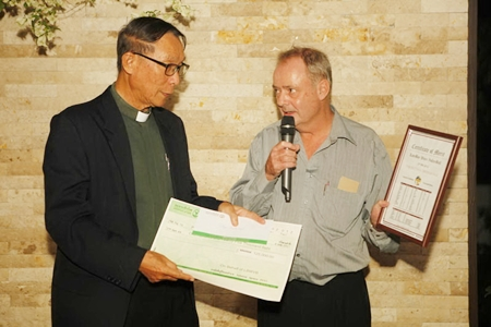 Father Michael, Director of Pattaya Orphanage (left), receives a cheque for 125,000 baht from tournament organizers.