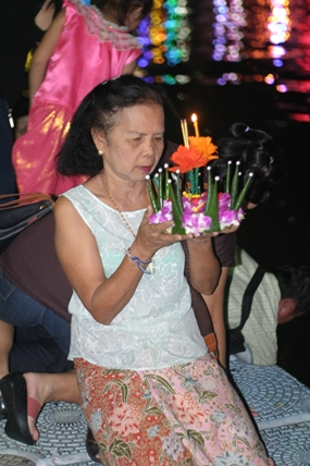 A grandmother with her family behind her prays before releasing her krathong.