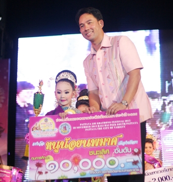 Waralak Uthaensut, 7, who won the Nang Noppamas contest at Bali Hai with her performance of Phra Baramee Maha Bhumibol (Virtuous King Bhumibol), receives her prizes from Mayor Itthiphol Kunplome.
