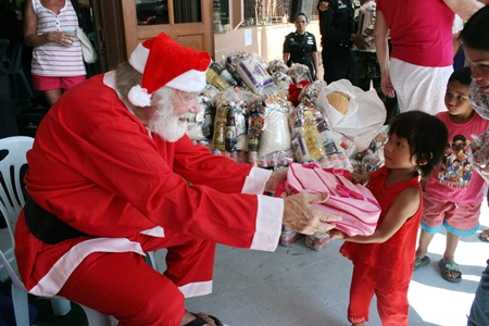 Santa Claus distributes gifts to thankful, but sometimes wary children.