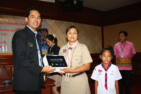 Mayor Itthiphol Kunplome presents one of the new tablet computers to a teacher and student from Pattaya School No. 1.