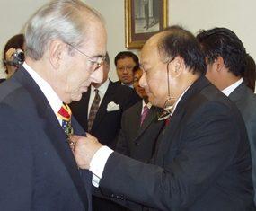 Baron Carini, left, receives his award from Ambassador Vikrom Koonpirochana.