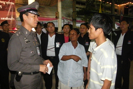 Somwang Rodkanphai (center) tells Pol. Maj. Gen. Khatcha Thatsart (left) about the attack on her 2 sons.