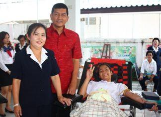 Banglamung District Chief Chaowalit Saeng-Uthai (center) and his wife Banglamung Red Cross President Nuanjan Saeng-Uthai (left) provide encouragement to Banglamung student donating blood.