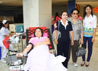 Nuanjan Saeng-Uthai, Banglamung Red Cross president, Mrs. Santana Mekavarakul, president of Mike Group, and Imjai Buncharoenkij, Banglamung Red Cross secretary, encourages a patient donating blood at Mike Shopping Mall.