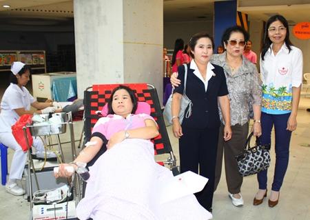 Nuanjan Saeng-Uthai, Banglamung Red Cross president, Mrs. Santana Mekavarakul, president of Mike Group, and Imjai Buncharoenkij, Banglamung Red Cross secretary, encourages a patient donating blood at Mike Shopping Mall.