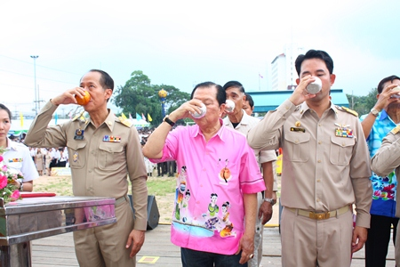 (L to R) Chonburi Governor Khomsan Ekachai, MP Santsak Ngampiches, chairman of the parliamentary Arts and Culture Committee; and Mayor Itthiphol Kunplome, drink blessed water to swear an oath to Their Majesties the King and Queen in the campaign against drugs.