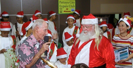 Board member Richard Smith thanks Santa for taking the time to visit & to give out presents to the children. Toy looks on.